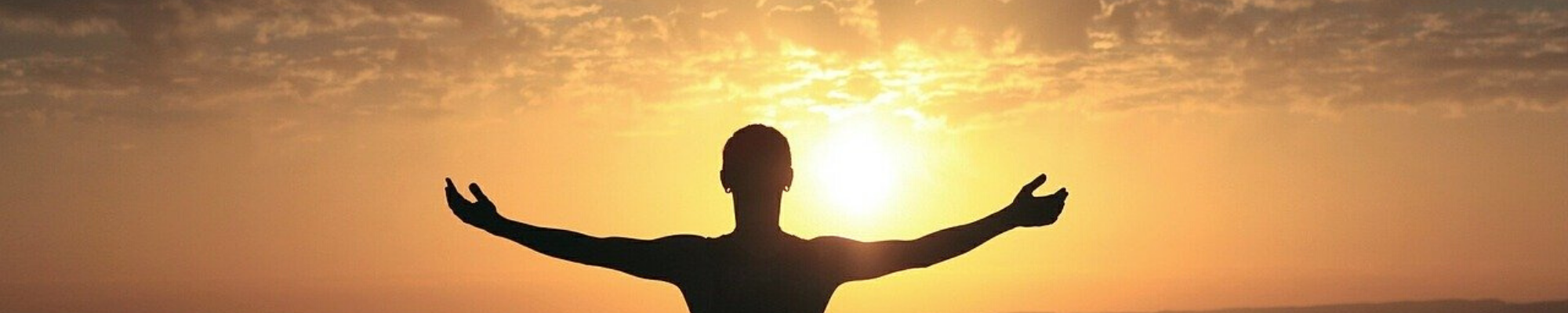 Silhouette of a person, arms open, welcoming the sunrise